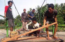 Masyarakat Kubu Anau Goro Perbaiki Lantai Jembatan Gantung